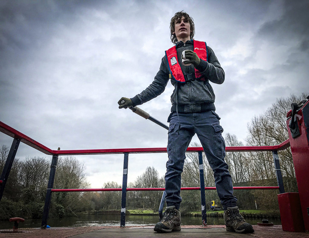 A young person steers a canal boat.