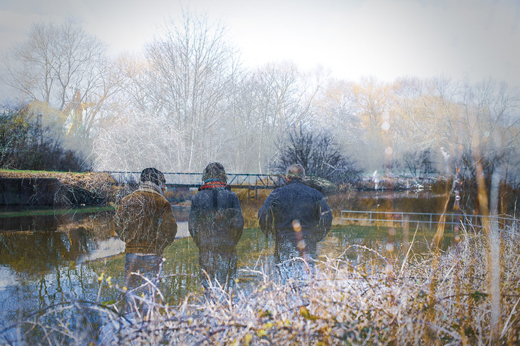 A young person and two boat crew members standing at side of canal.