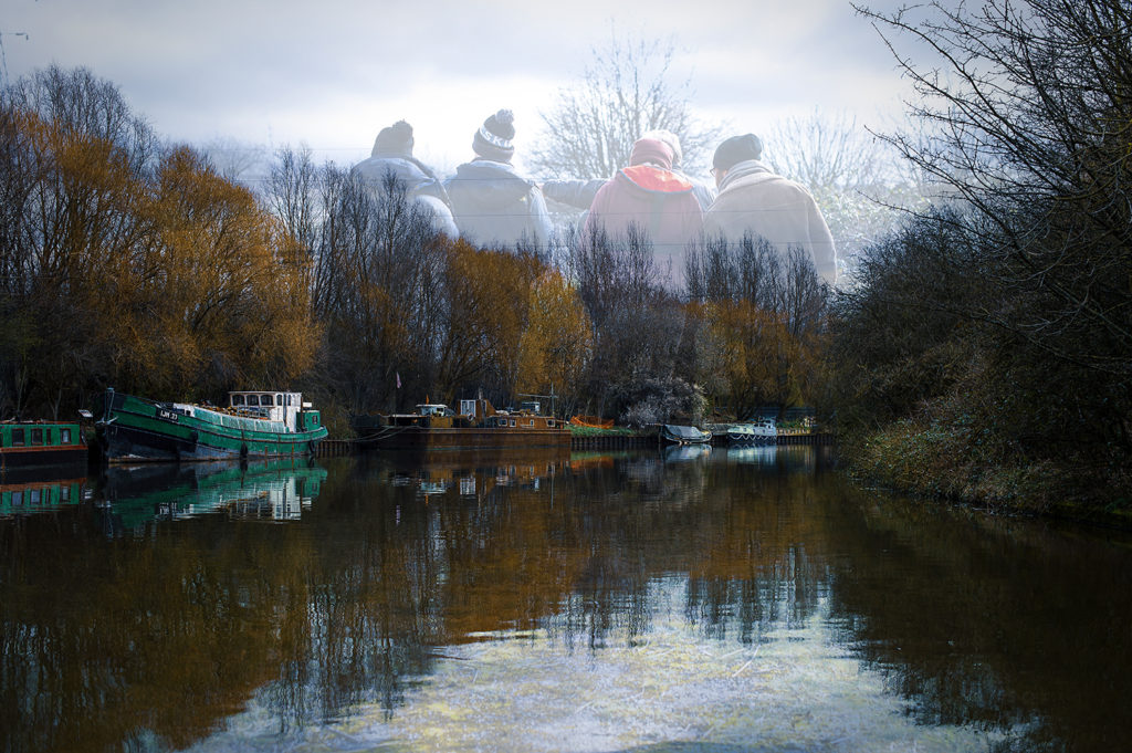 Two young people and two boat crew members standing at side of canal.