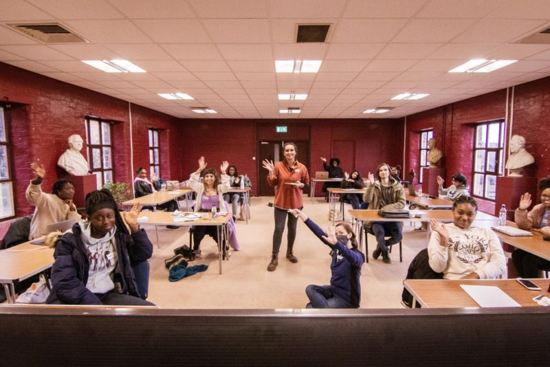 A room of young people wave to the camera